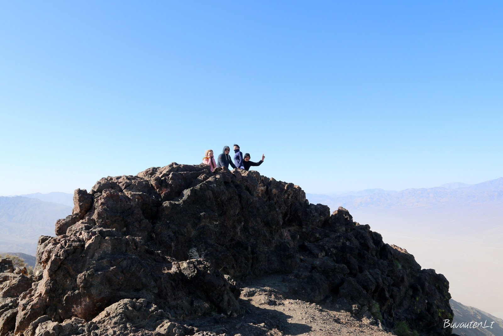 Sužvarbę draugai vėjuotoje kalno viršūnėje