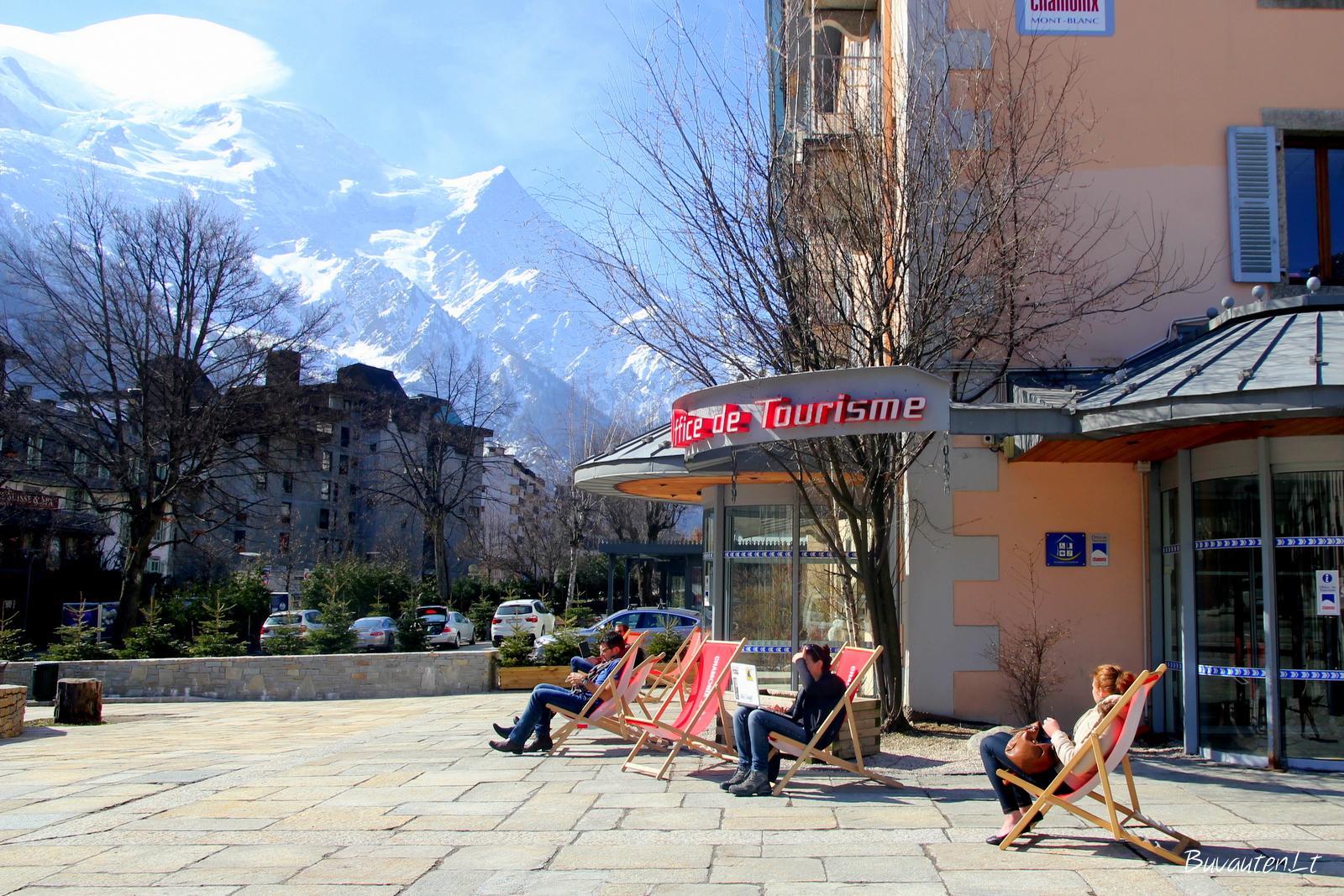 Turistai šalia turizmo biuro gaudo pavasario saulę