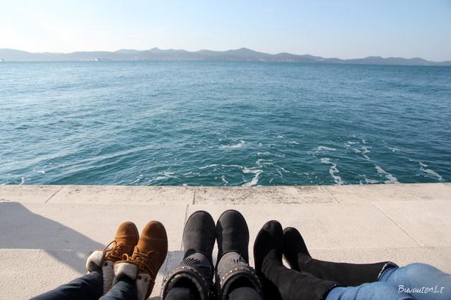 Poilsis prisėdus ant laiptelių prie jūros instrumento