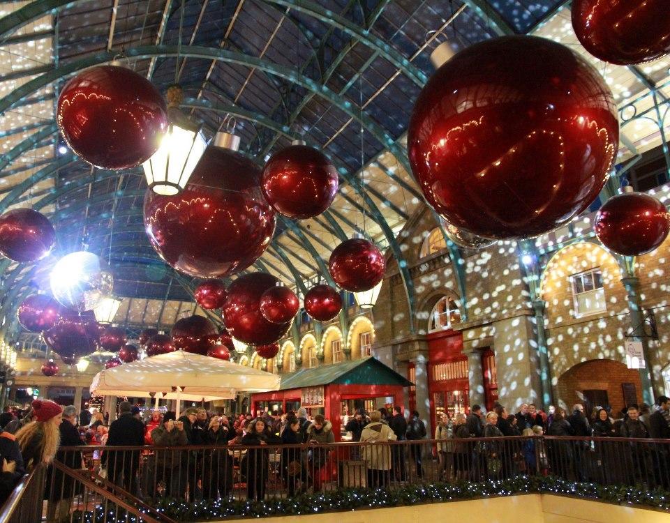 """Covent Garden """"obuolių"""" turgus (Apple market) kasmet šventėms pasipuošia didžiuliais raudonais burbulais"""